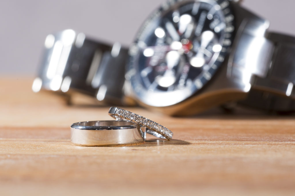 Silver watch and wedding rings on a wooden table