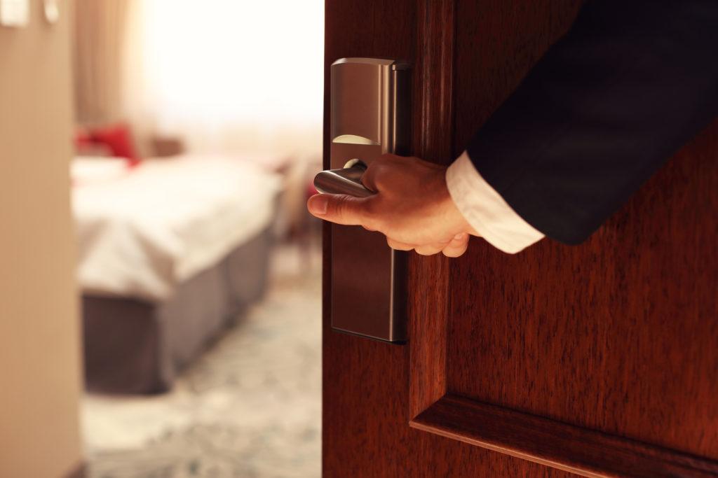 Man holding open hotel room door