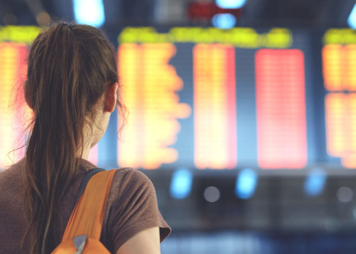 Woman reading departures at departure board