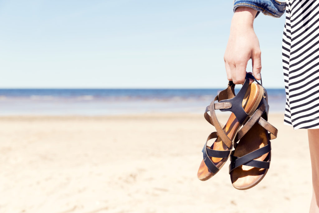 Person holding a pair of sandals in one hand on a beach