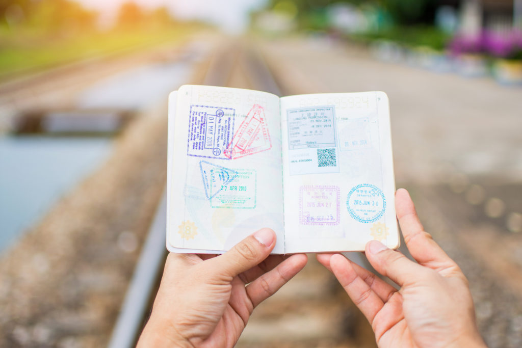 Hands holding a passport open to pages full of stamps