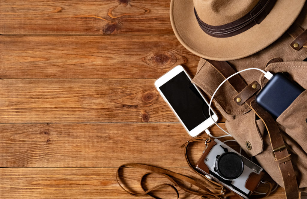 A backpack on a wooden background with a phone, power pack charger, a camera, and a hat spilling out of it