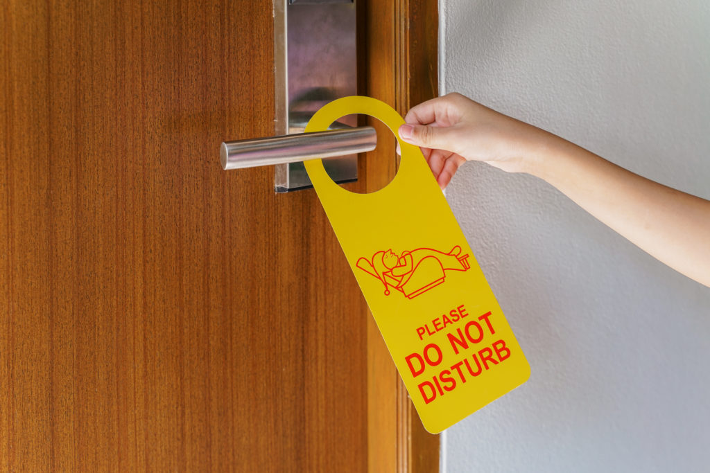 Person hanging a Do Not Disturb sign on hotel room door