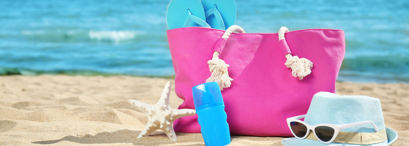 Pink beach bag with blue accessories on the beach