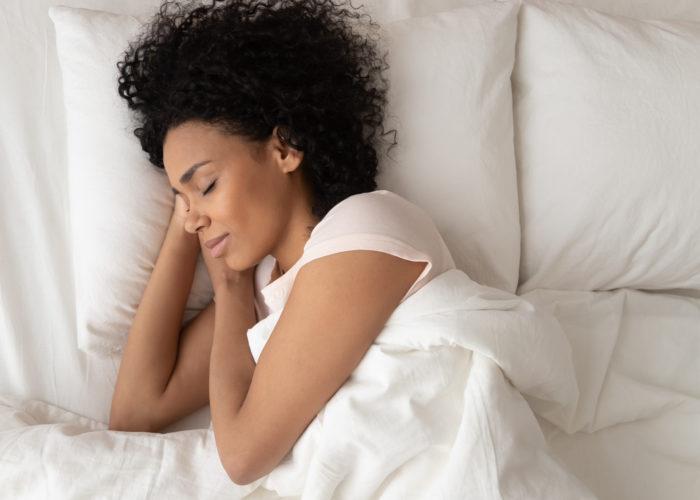 Woman asleep on comfortable bedding