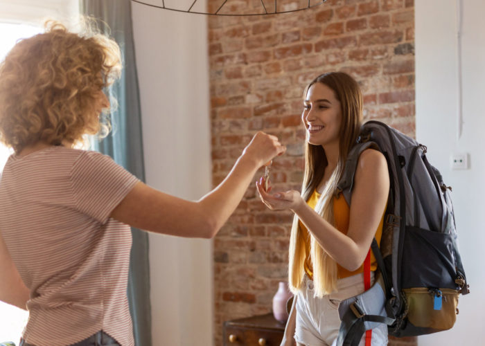 Young traveler with backpack gets keys to apartment rental