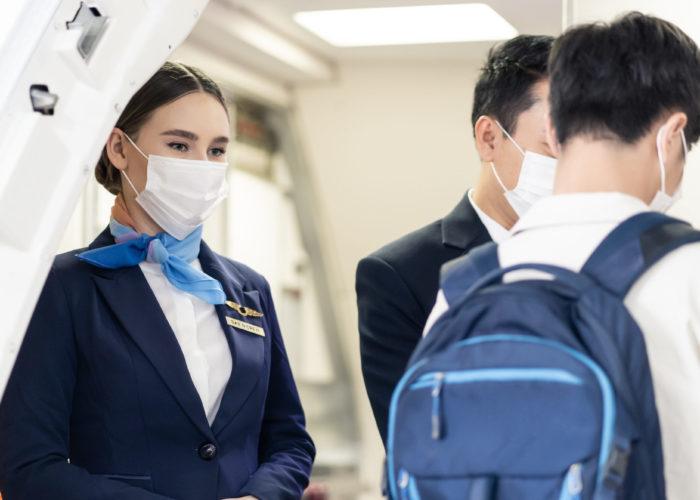 Masked flight attendant greeting passengers