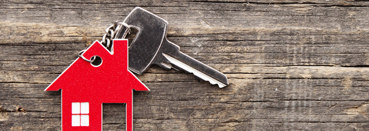 House key with red house-shaped keychain on a wooden background