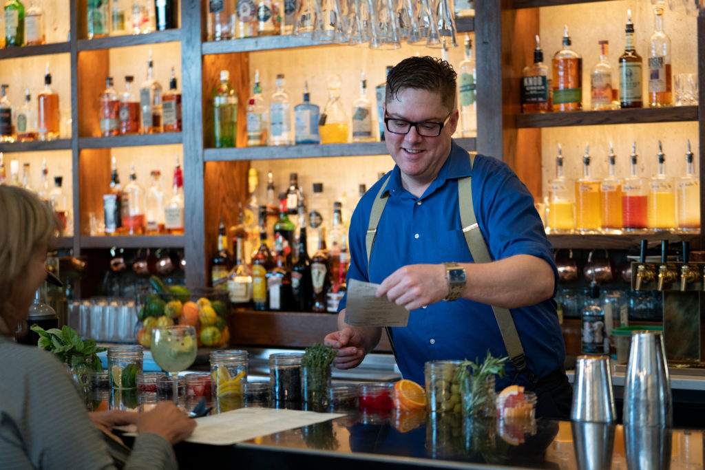 Bartender taking an order from behind a well stocked bar