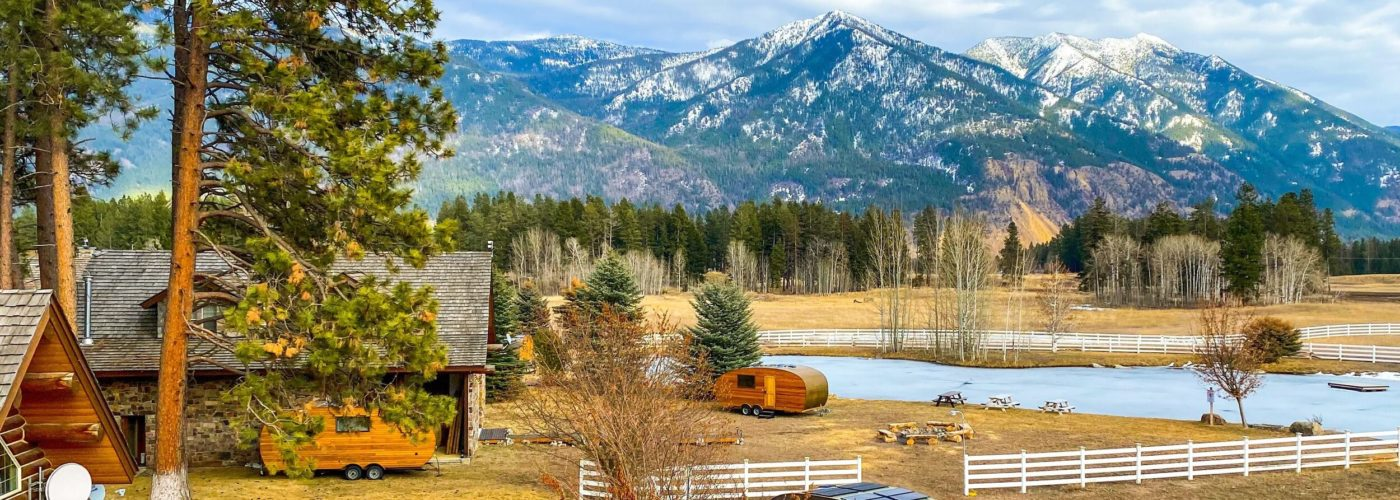 Two cabins and two small wooden trailers surrounded by trees on a backdrop of tall mountains at ROAM Beyond