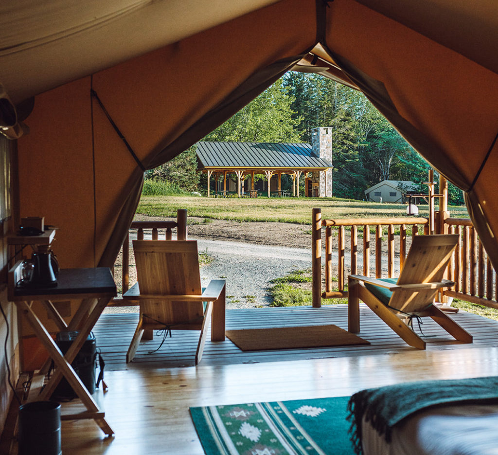 The inside of a glamping tent at Terramor Outdoor Resort in Bar Harbor, Maine, looking out over the grounds