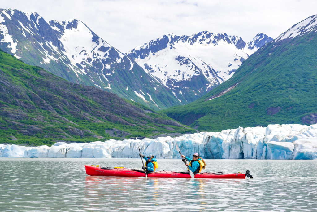 Two people kayaking next to Spencer Glacier outside of Anchorage, Alaska