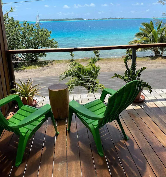 Two green chairs on a deck facing out toward a beach and ocean view in Bora Bora, French Polynesia