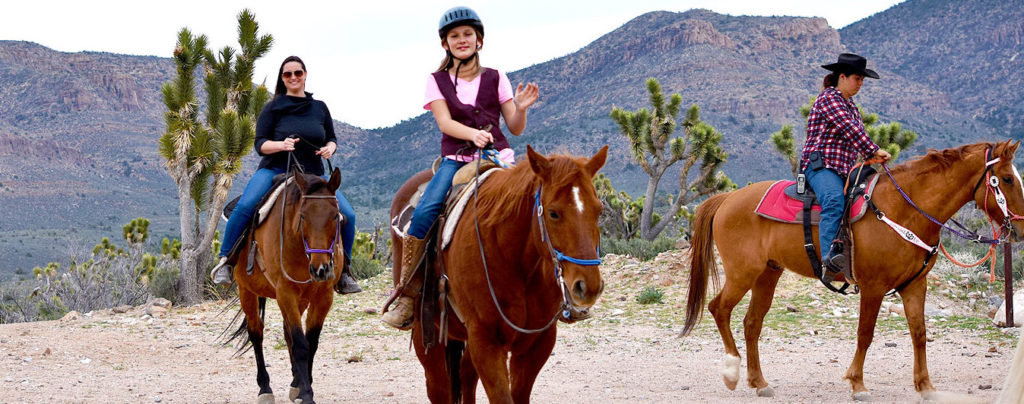 Three people riding horses at the Grand Canyon Western Ranch