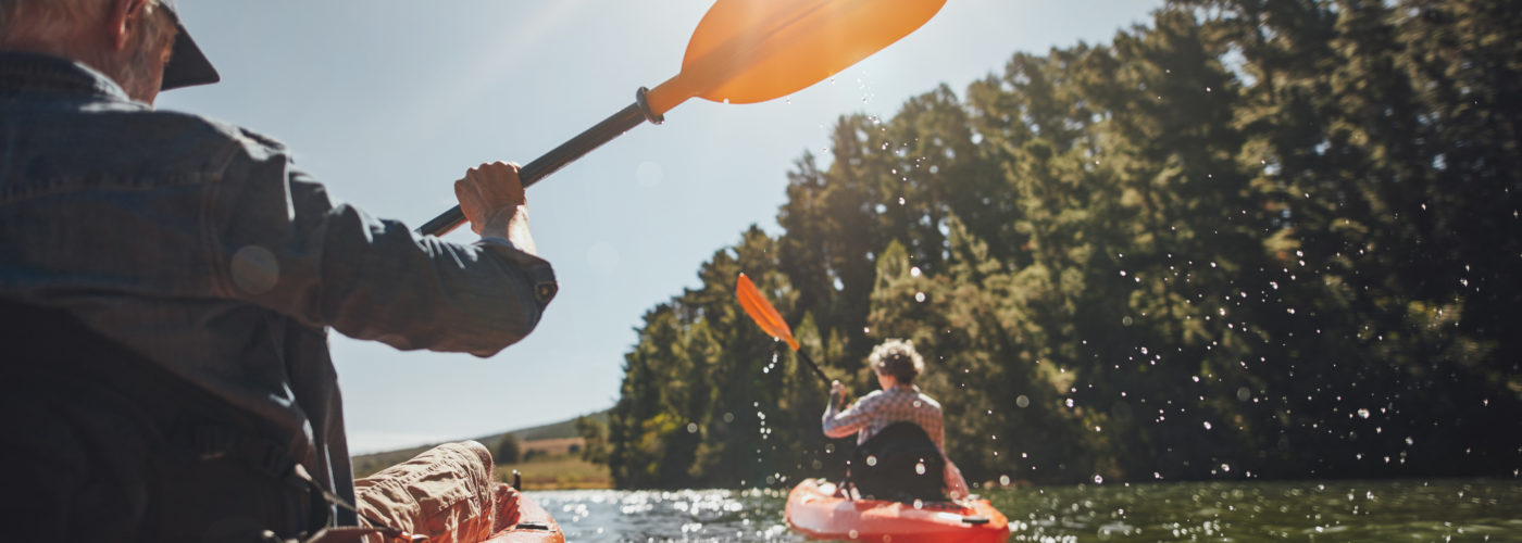 Two people kayaking on a lake on a sunny day