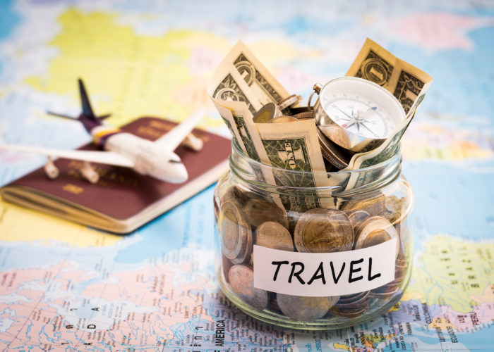 """A jar of money labeled """"Travel"""", a passport, and an airplane figurine on a colorful world map"""