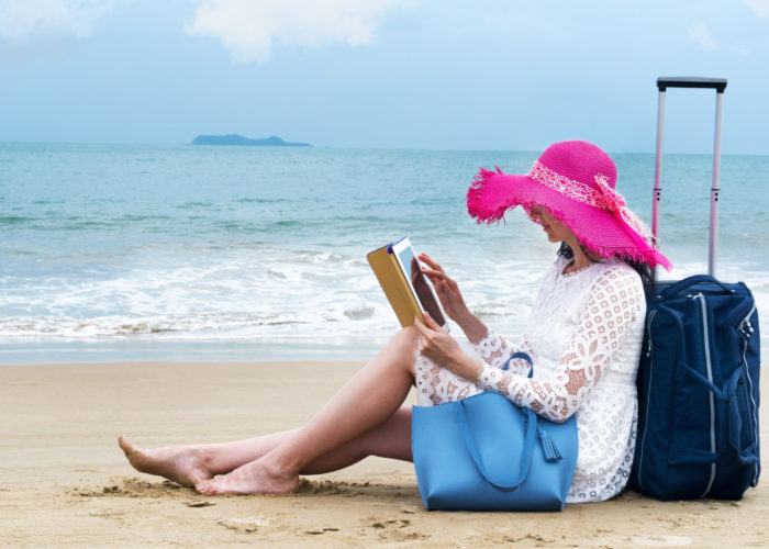Tourist reclining against her luggage on the beach, reading on her iPad
