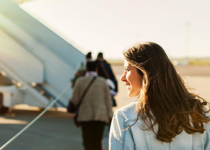 Woman walking towards a plane on the tarmac to board