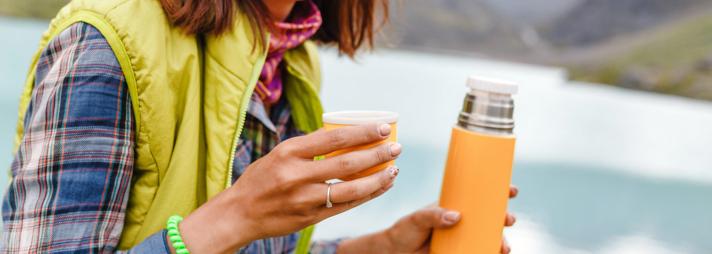 Woman sitting outside drinking from an orange travel thermos