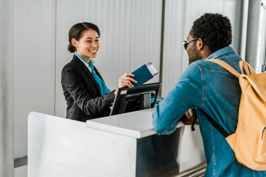 Flight attendant hands passport and boarding pass back to tourist with backpack