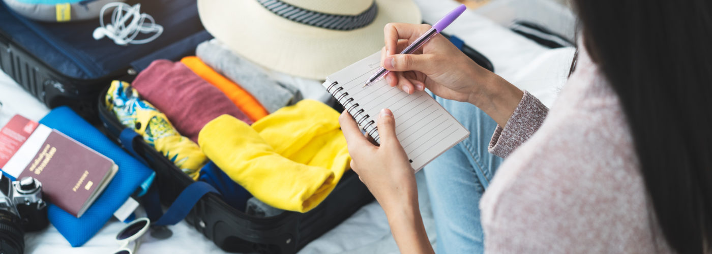 Woman makes a packing list on a small notepad while packing a suitcase