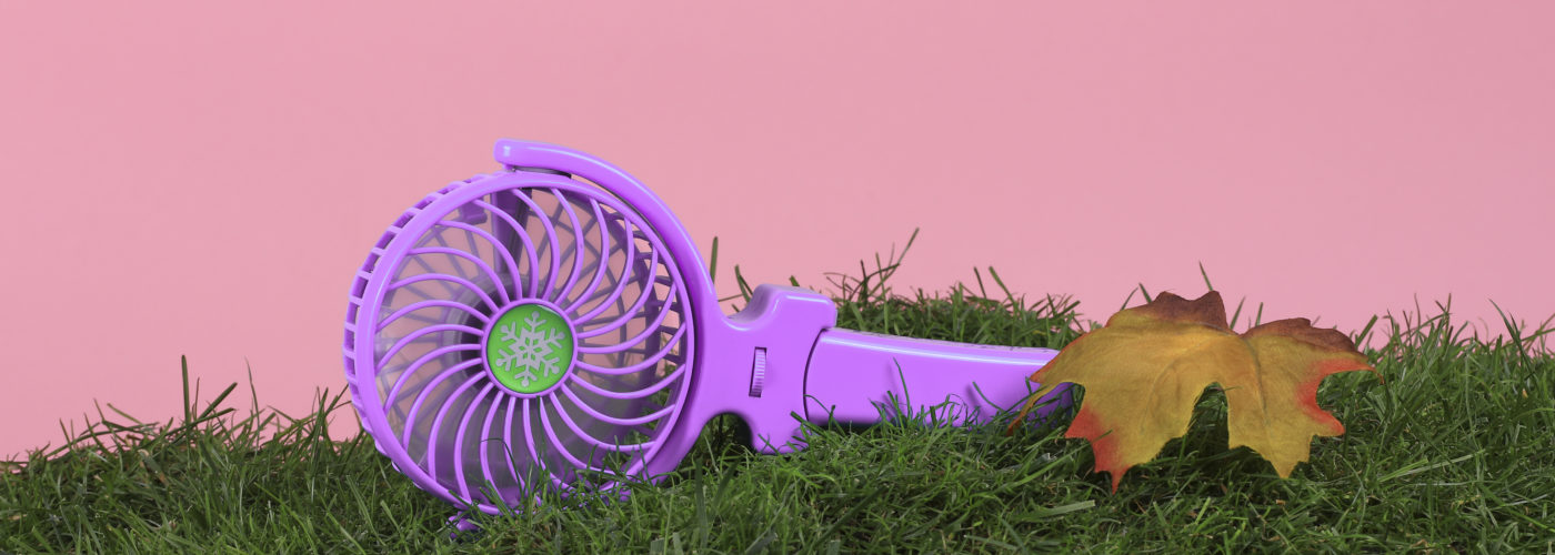 Handheld electric fan on a bed of grass with a pink backdrop