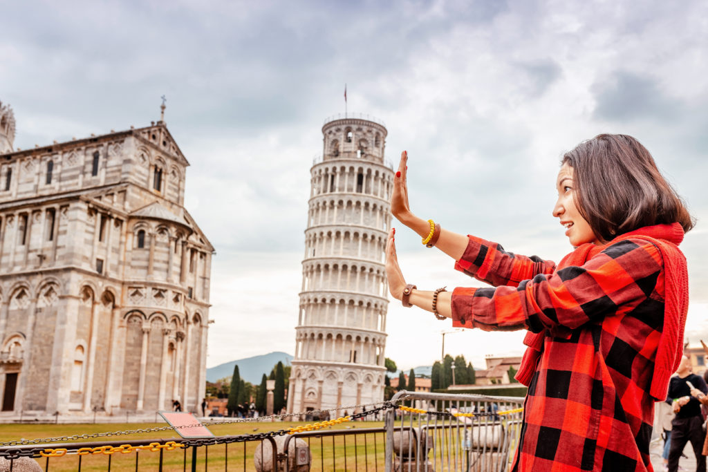 Woman pretending to hold up the Leaning Tower of Pisa