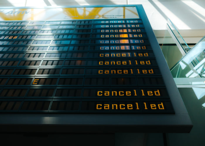 Departures and Arrivals board showing flight cancellations