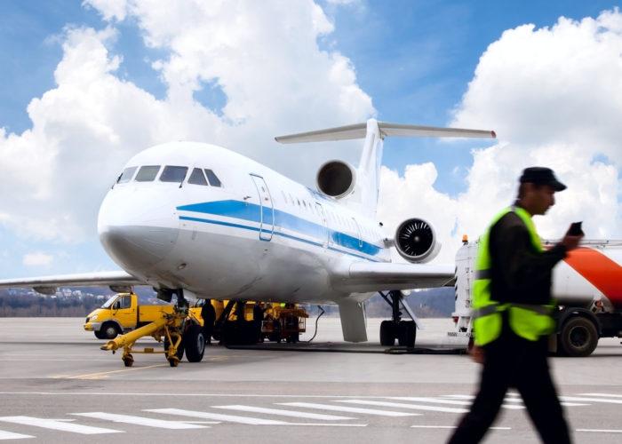 Man walks across a crosswalk on a tarmac in front of a passenger plane