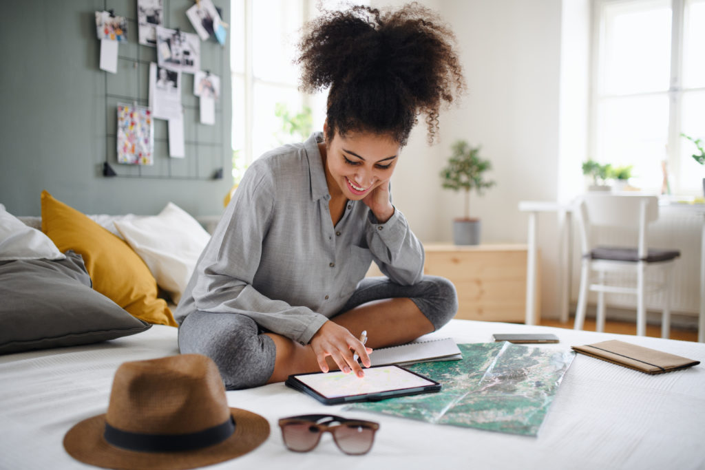 Woman sitting on a bed and working on tablet surrounded by a map, sunglasses, a hat, and small pocket books