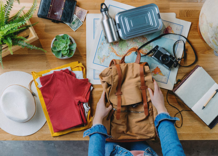 Hands packing a backpack with sustainable travel gear surrounding them