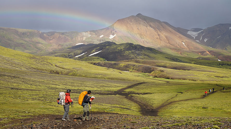 Six hikers, two in foreground and three further away, on a hiking path through rolling hills with a rainbow overhead