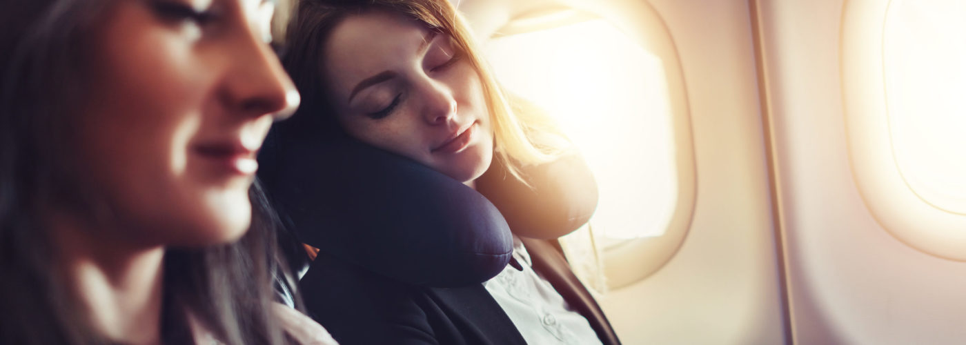 Woman sleeping using a neck pillow in a window seat on an airplane