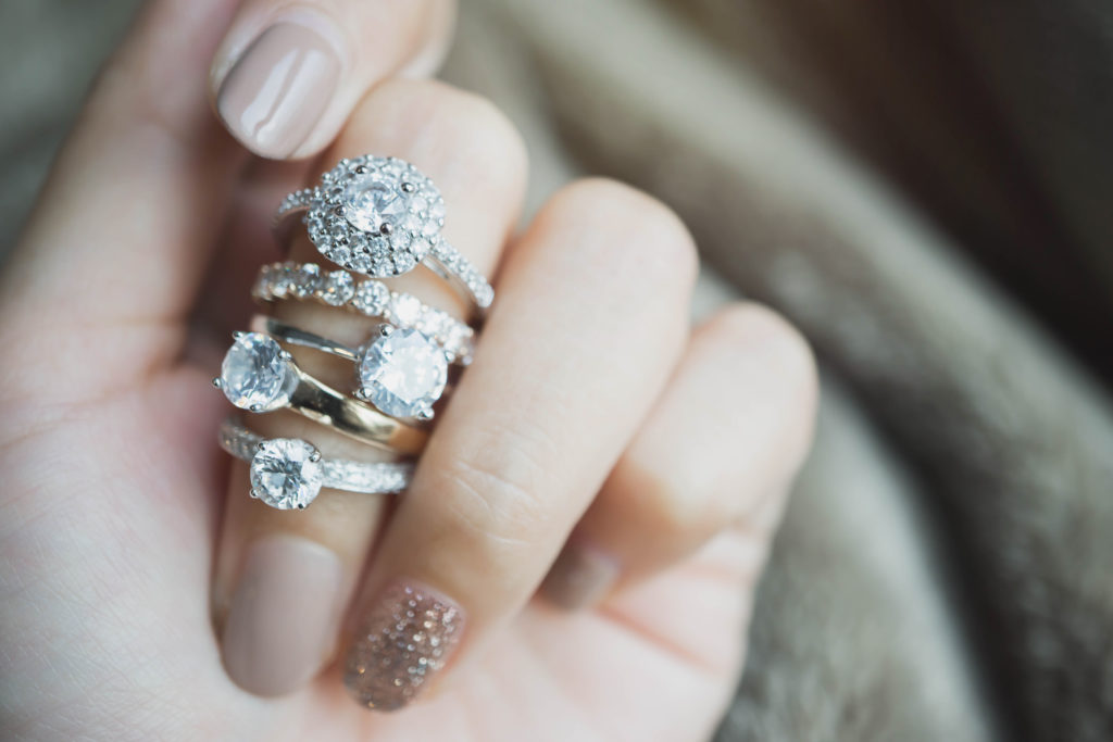 Close up of hand with multiple diamond rings on one finger