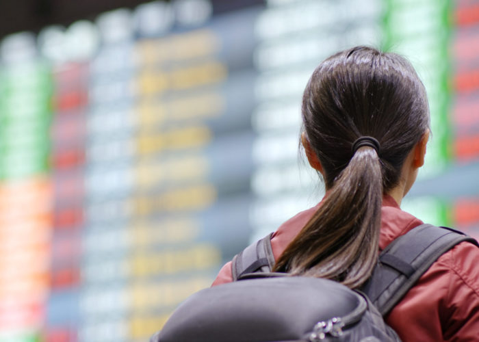 Woman with backpack reading the arrivals board at an airplane