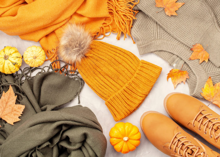 Flat lay with fall clothes, shoes, pumpkins, and leaves