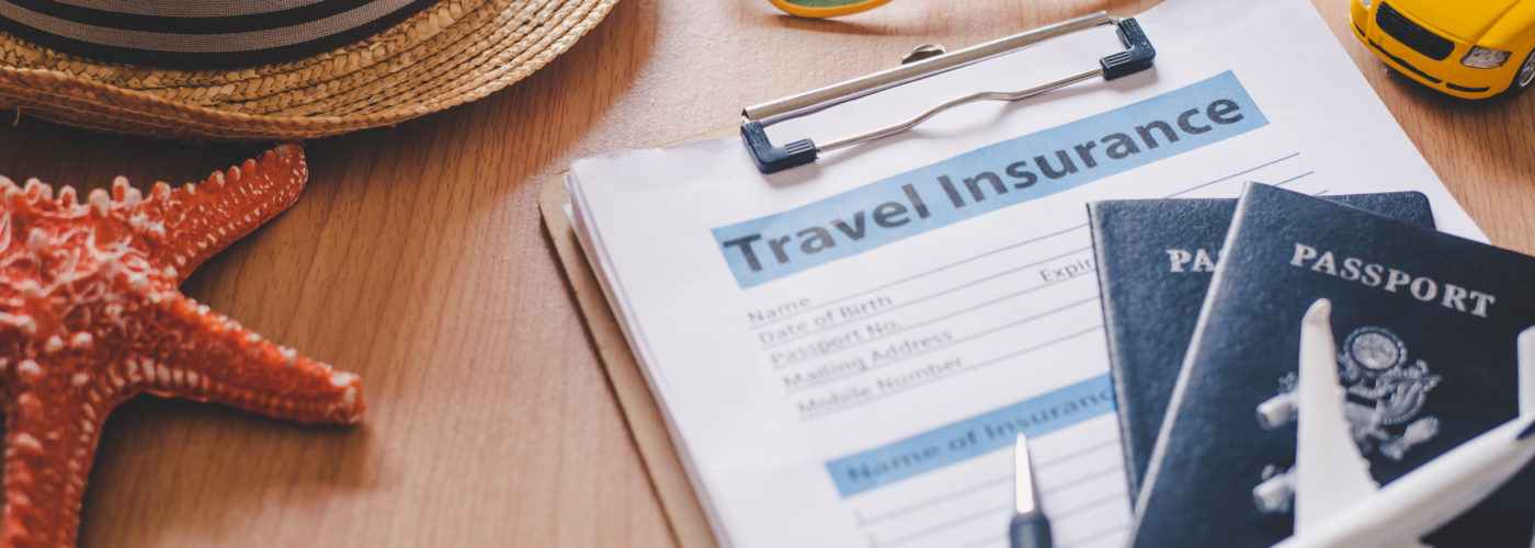 Travel insurance forms on a table surrounding by travel items