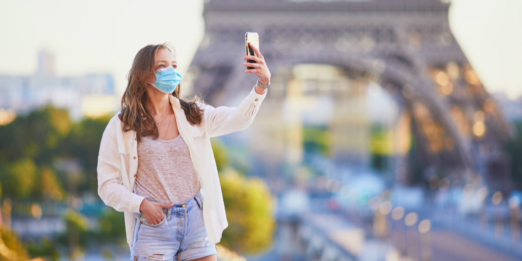 Woman taking a selfie wearing a facemask in front of the Eiffel Tower