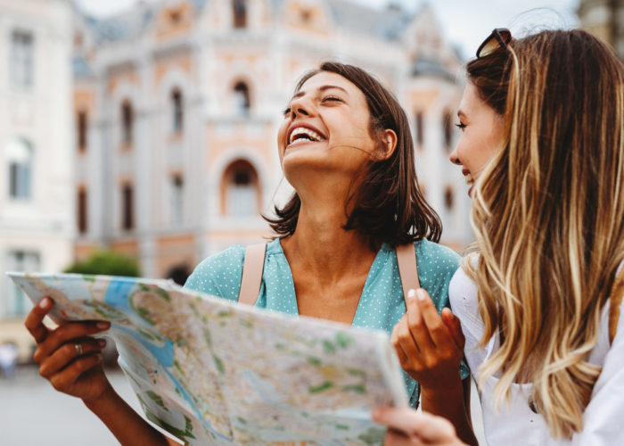 Two women laughing a reading a map in a European city
