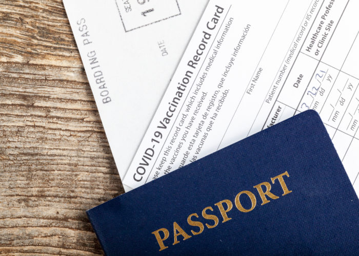 Passport, COVID vaccination card, and boarding pass on a wooden background