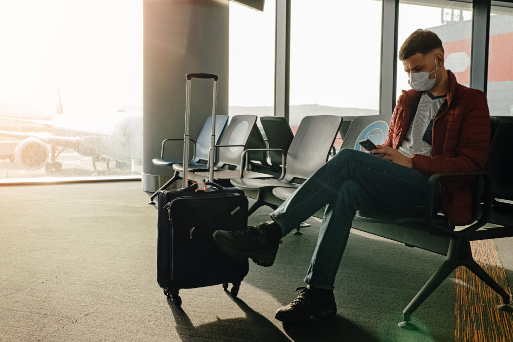 Man waiting on his phone with suitcase at airport terminal