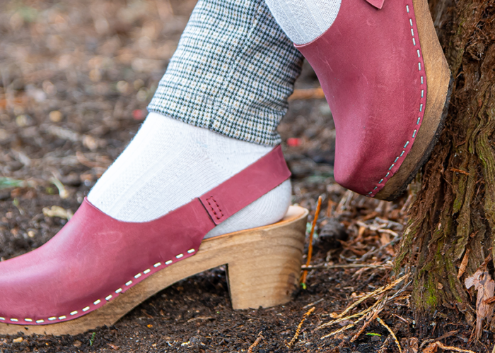 Person, viewing from the ankles down, wearing pink clogs leaning up against a tree