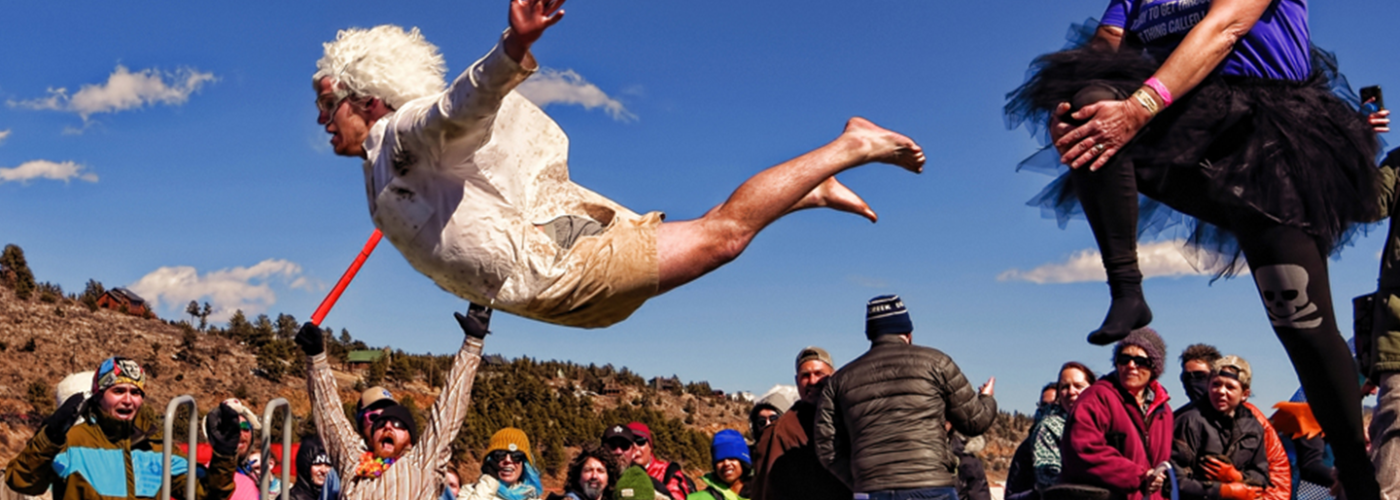 Man jumping from a platform while a crowd cheers on at Frozen Dead Guy Days festival