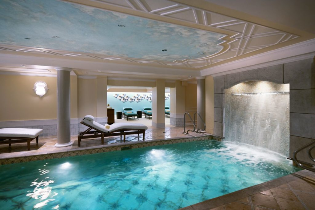 Pool and waterfall surrounded by lounge chairs at the Kohler Waters Spa
