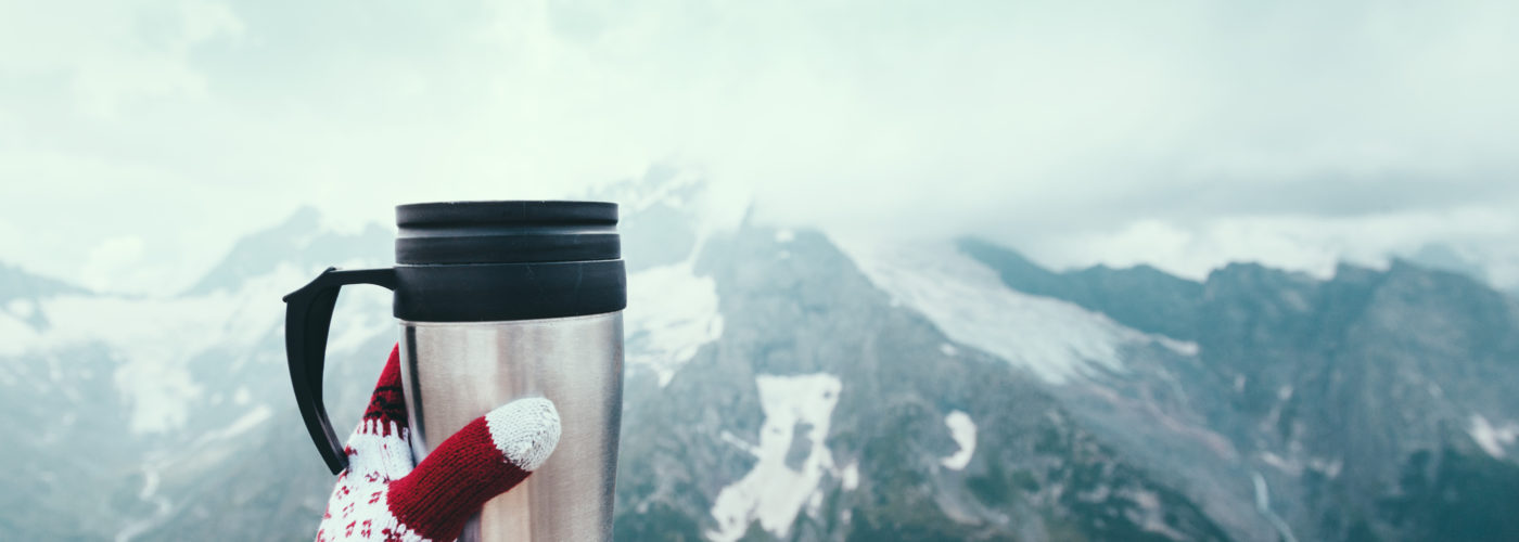 Point of view shot of a person holding a thermos of tea against a mountain backdrop