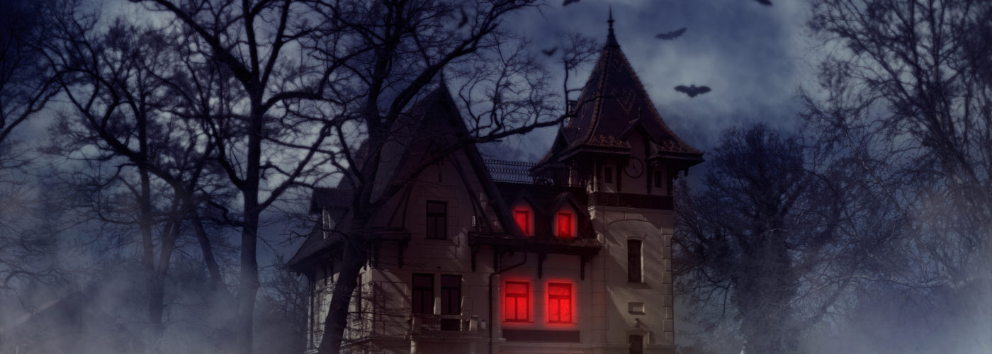 Haunted house on a hill with red lights shining inside and bats flying overhead