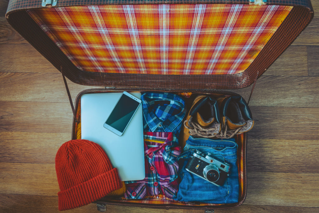 Open suitcase with laptop, phone, shoes, and clothes