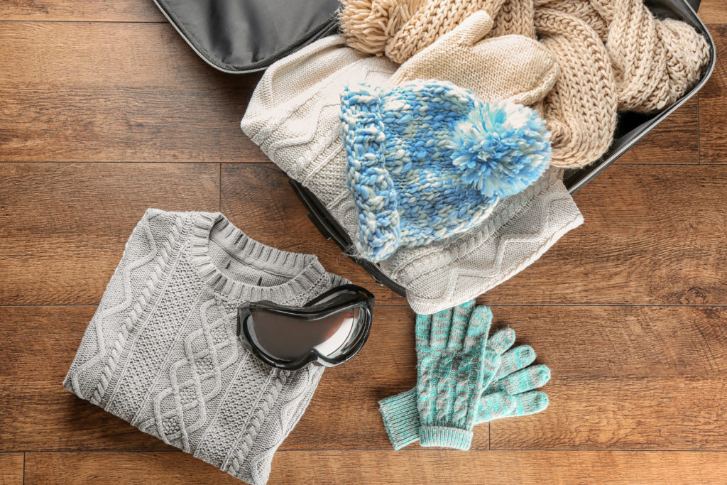 An open suitcase full of winter clothes on a wood floor backdrop