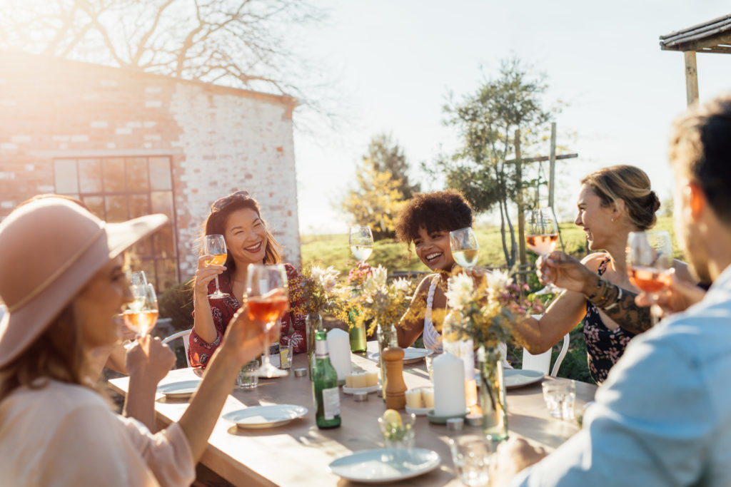 Group of friends toasting with wine glasses at outdoor dining table
