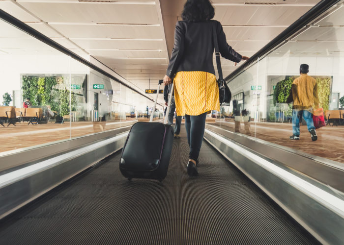 Woman rolling a suitcase down an automatic walkway in an airport